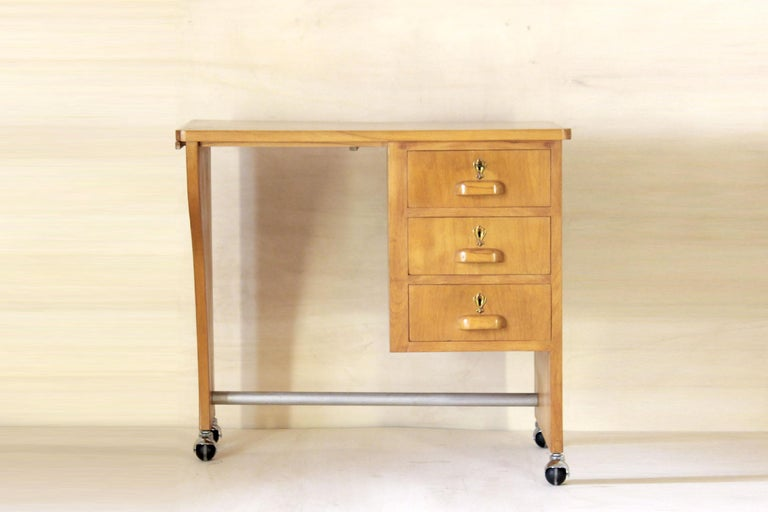 A solid wood bright rolling writing desk from the 1960s in pure midcentury style. The item is in very good conditions as the wood has been cleaned and polished and original small wheel have been replacing with brand new ones. Only small beautiful