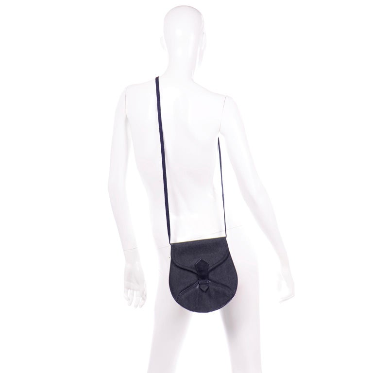 This is a really timeless vintage 1970's Yves Saint Laurent Rive Gauche designer handbag in navy blue grain leather with a fabric shoulder strap. The bag has a front flap closure and an inside open pocket. This classic YSL vintage shoulder bag