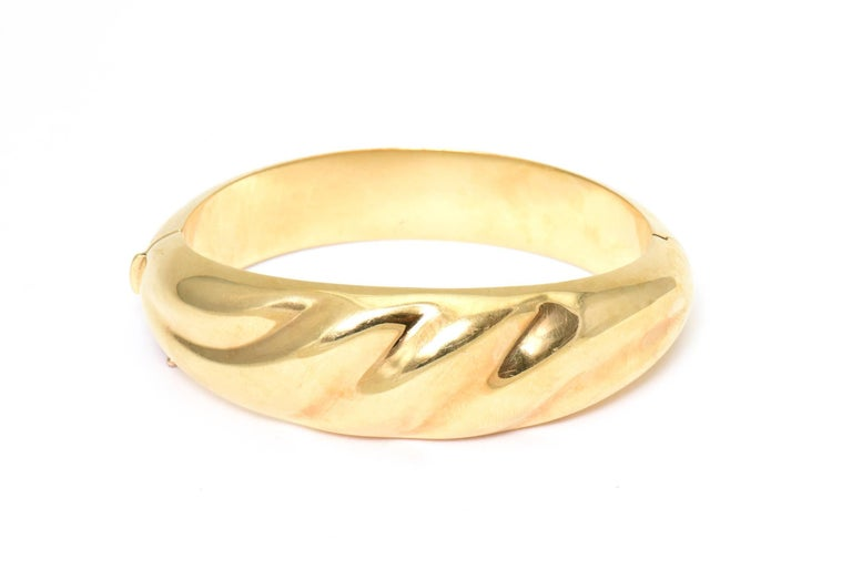 1970s Hinged 18k yellow gold bangle bracelet with a 3 dimensional wave design.  This bracelet was cast in Italy.  It has a push button clasp as well as a figure 8 safety.  Interior circumference 6.5
