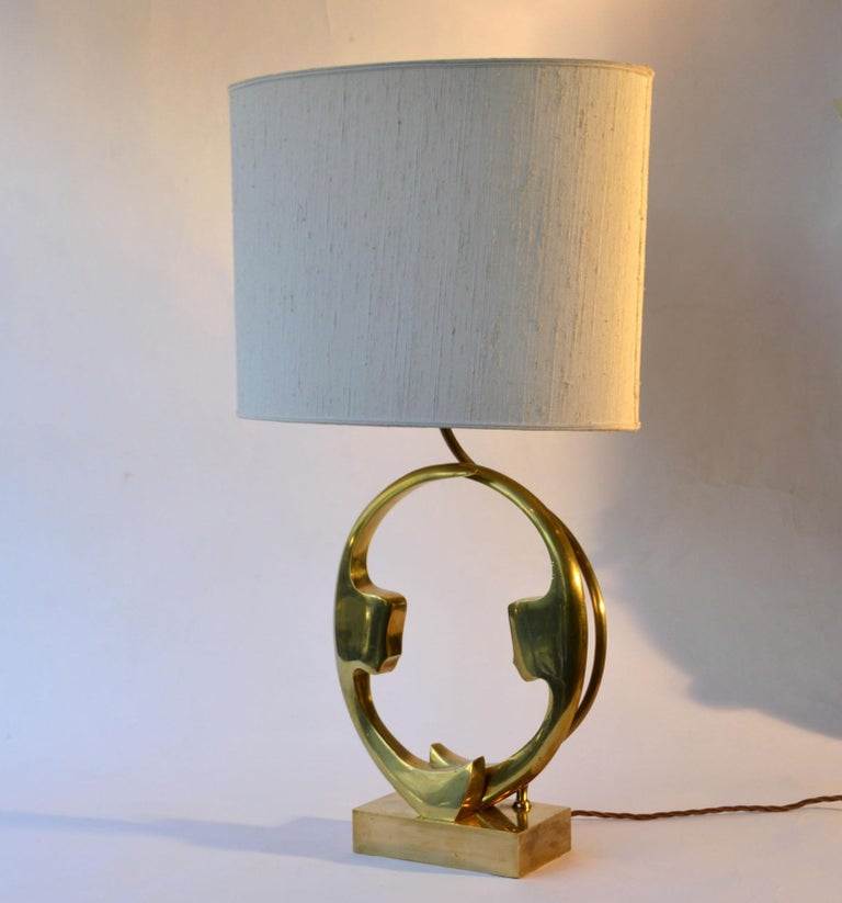 Single brass and bronze cast table lamp signed Willi Daro, Belgium 1970s picturing two female silhouettes faces facing each other on an oval ring. with original oval lampshade. Belgian artist Willy Daro founded his factory