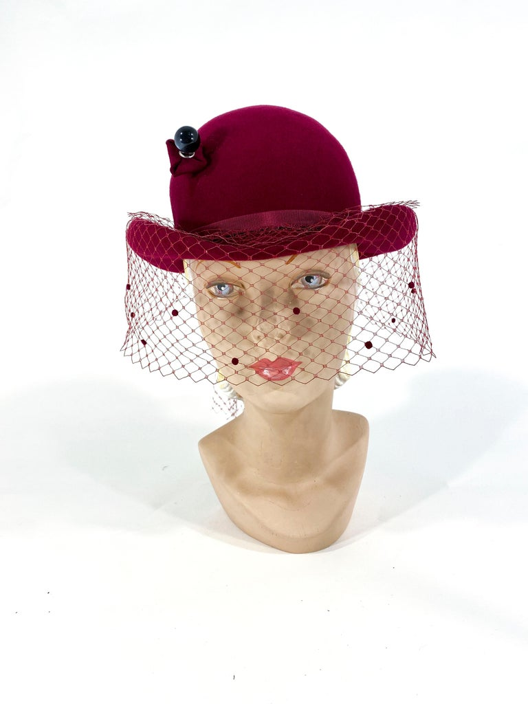 1970s wine colored felt derby with an enlarged decorative hatpin, a grosgrain band, and a veil that theres in the back finished with a 6-inch drape.