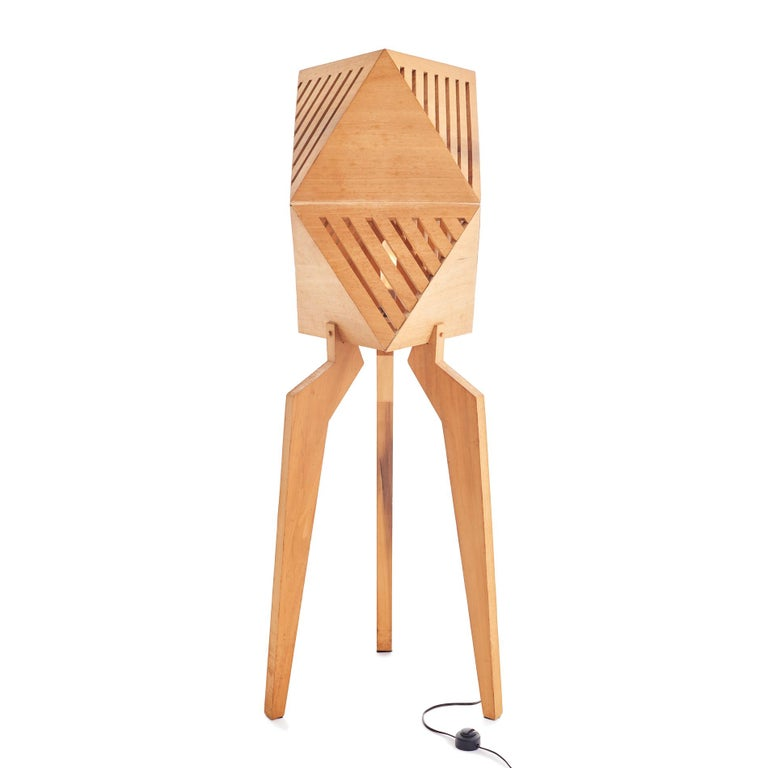 Gorgeous 1970s studio craft wood tripod lamp. The faceted top portion features alternating solid surfaces and slats, allowing the inner lightbulb to emanate a soft glow. Three angled legs give way to a cord with original push button operation.