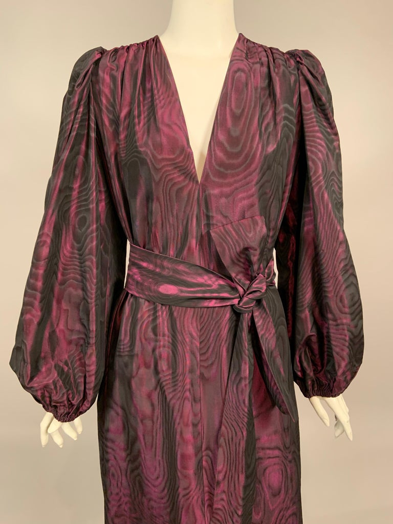 Yves Saint Laurent chose a striking fabric for this dress or caftan from the 1970's. Aubergine and black moire changes color intensity with the light, more purple or more black as you move through the evening. The dress has a plunging V shaped