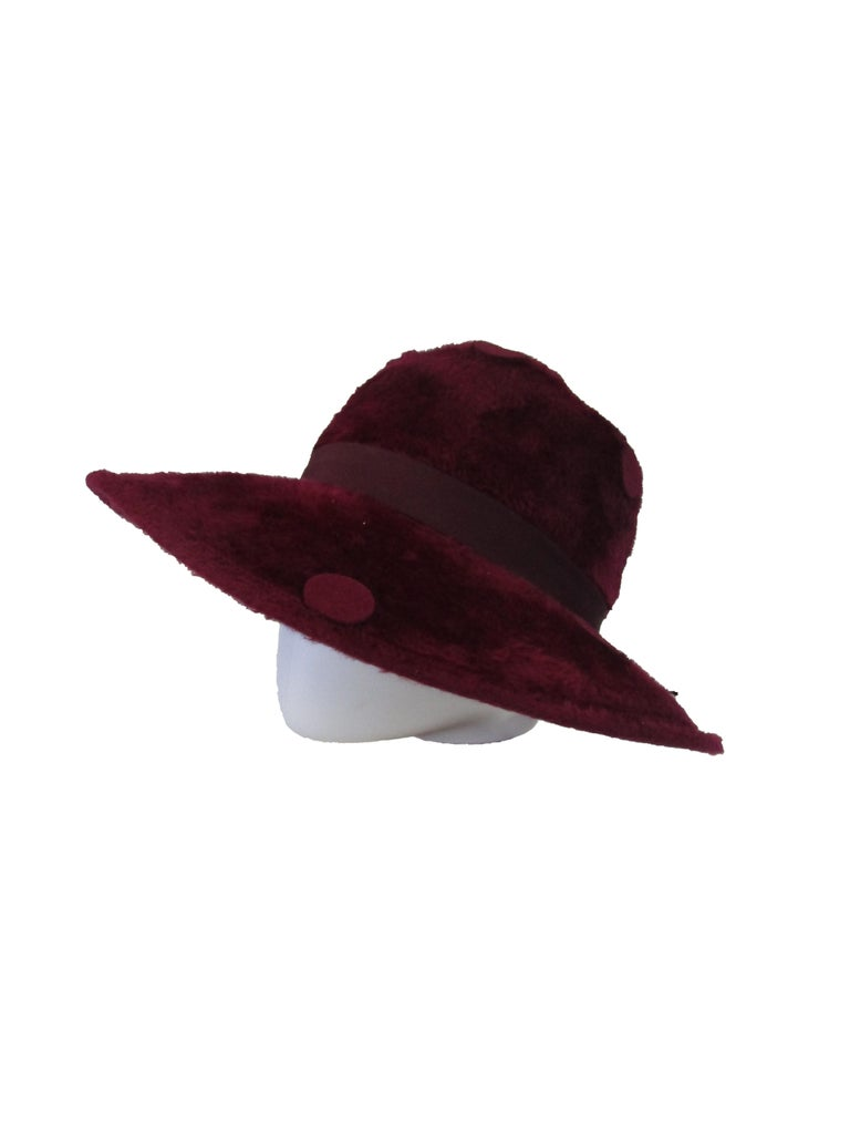 Check out this effortlessly cool hat from Yves Saint Laurent that will easily liven up your wardrobe! The body of the hat is a wine red *faux* fur that is decorated with large felt dots throughout. A deep red grosgrain band wraps around the hat