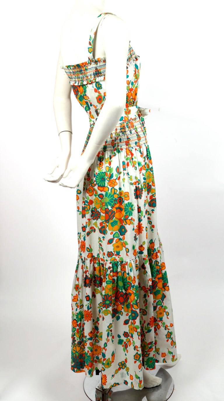Very rare white cotton floral printed dress with multi-colored hand-stitching and long waist tie from Yves Saint Laurent dating to the 1970's. Labeled a French size 36. Approximate measurements: up to a 33