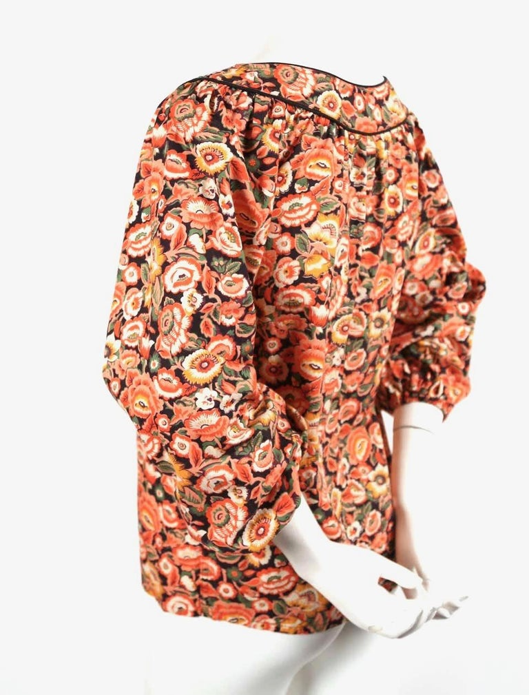 Vivid, floral-printed, cotton peasant shirt with black piping and elasticized cuffs designed by Yves Saint Laurent dating to the 1970's. Labeled a French size 34. This shirt best fits a size 0 through 4. Approximate measurements: shoulder 14-15