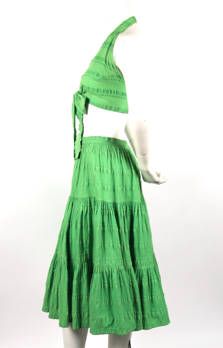 Matching crop top and tiered skirt in lime-green seersucker cotton designed by Yves Saint Laurent dating to the 1970's. Top is labeled a size 2 and skirt is a 38 although both pieces have been altered. Top is adjustable and skirt measures