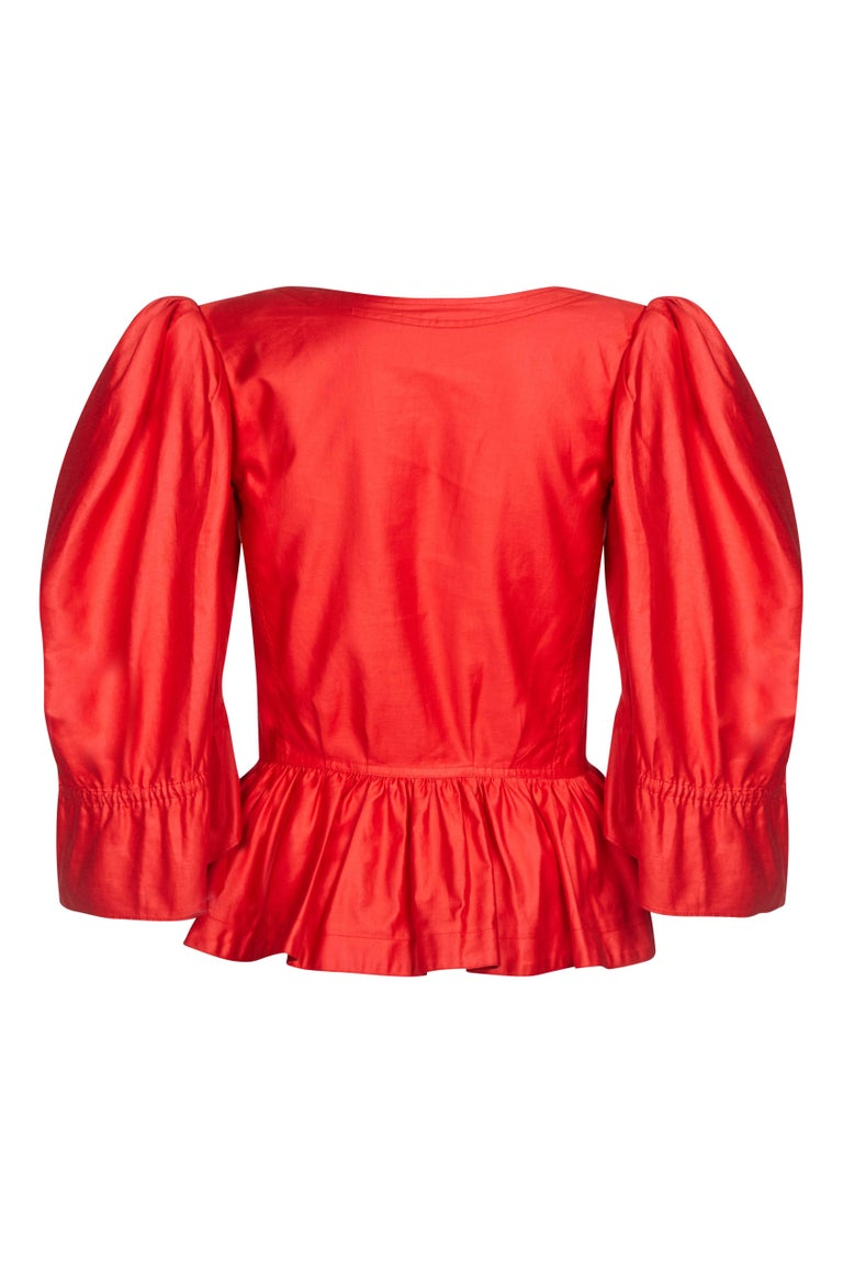 This vibrant 1970s Yves Saint Laurent red polished cotton blouse is guaranteed to turn heads. The deep red colour, bold puff shoulder feature, lavish bell sleeves and peplum detail makes this something of a statement piece. The bodice is beautifully
