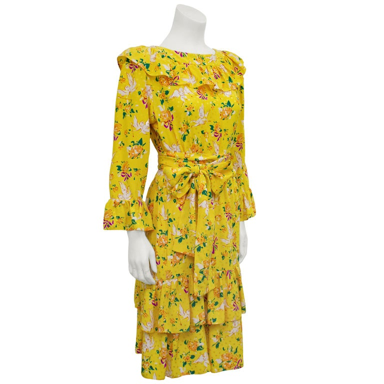 Early Yves Saint Laurent bright yellow, long sleeve, silk jacquard dress from the 1970s. Monochromatic yellow silk with yellow polka dots allover. Print includes cute white cupids, orange, green and red flowers with purple bows. Large ruffle at