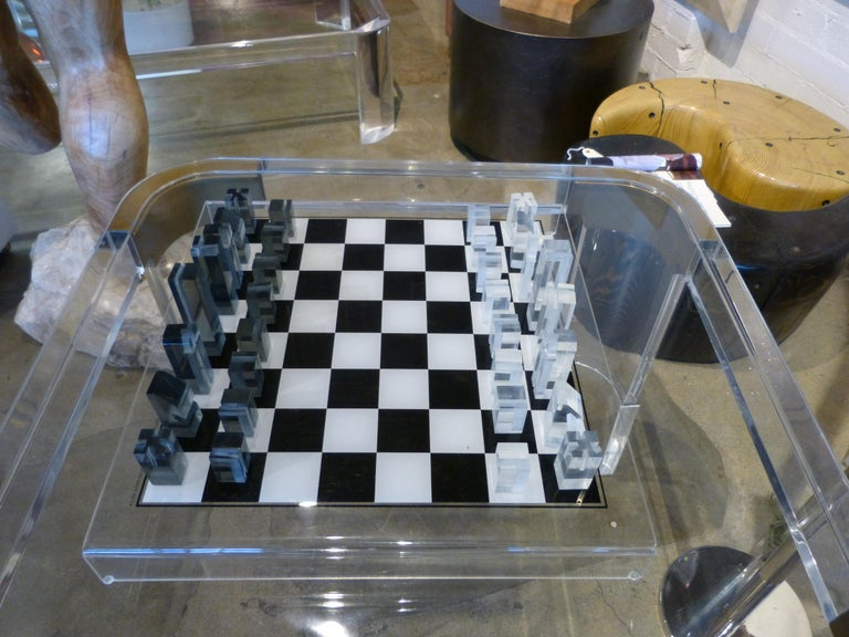 A nice raised acrylic chess board with light and dark chess pieces. It is marked 1973 Executive Games inc, Boston Mass. There is a bit of marks to the board the worst of which are pictured. The chess pieces also have some age appropriate wear. the