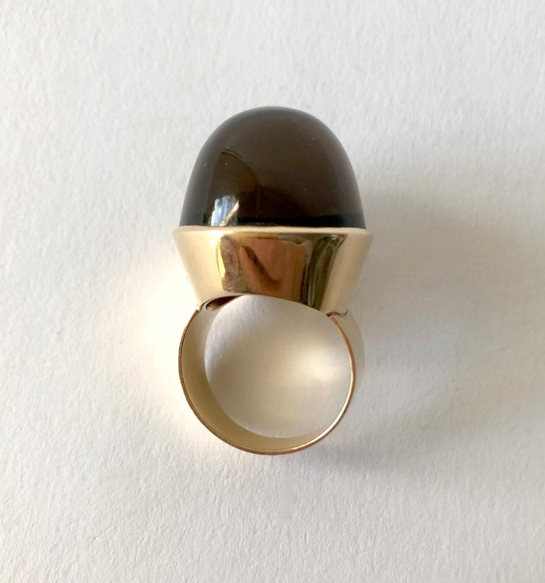 A high domed ring with oval cabochon of smoky quartz set in 14 karat rose gold created by Kaunis Koru of Finland.  Ring size is 7.25 to 7.50.  Signed with the maker's mark for Kaunis Koru, 585, and V7 (1974).  In very good vintage condition. 17.8