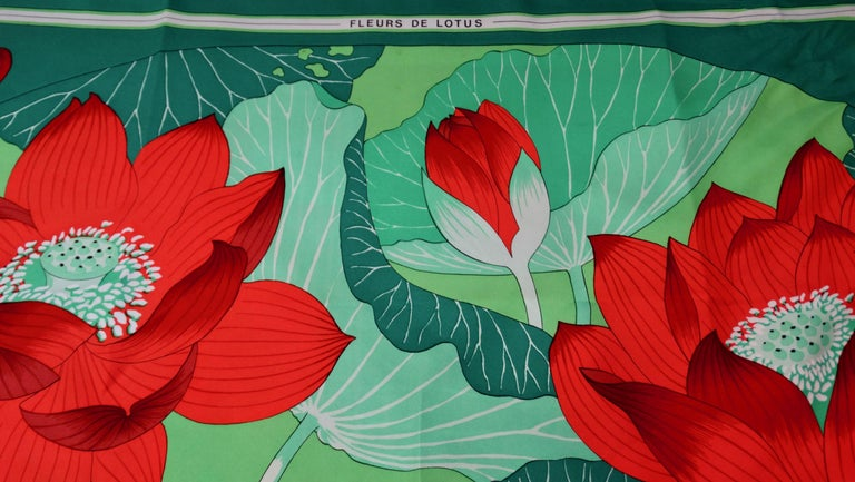 We all need a great Hermés scarf! Circa 1976, this 100% Silk scarf features a beautiful motif designed by Christiane Vauzelles titled, 'Fleurs De Lotus.' Includes large red lotus flowers surrounded by various contrasting shades of green vegetation.