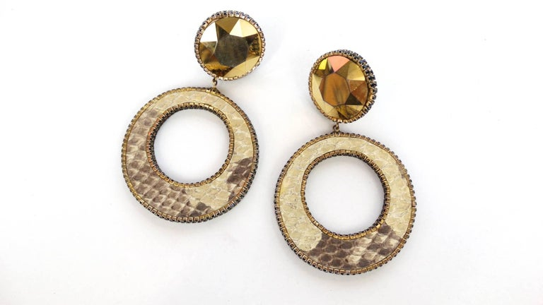 A fabulous pair of Deanna Hamro python hoop earrings. look at the details the edges are trimmed with small black rhinestones adding a great finished look. These earrings are 4 inches long by 2 inches wide. Clips are secure signed Deanna Hamro Los