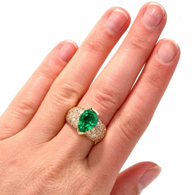 This opulent and timelessly elegant cocktail ring with a 4.01 carat GIA certified brilliant-cut pear shape emerald and pave diamonds is crafted in solid 18-karat yellow gold, weighing 11.42 grams and measuring 14 mm wide. The natural beryl emerald