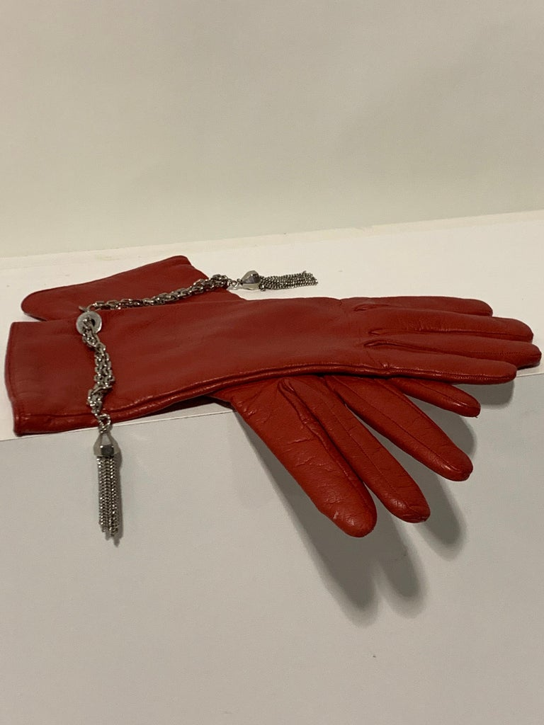 1980s Gianni Versace deep crimson red lambskin leather gloves, lined in cashmere knit with chrome chain and tassel detail at wrists. Size 8. New, never worn.