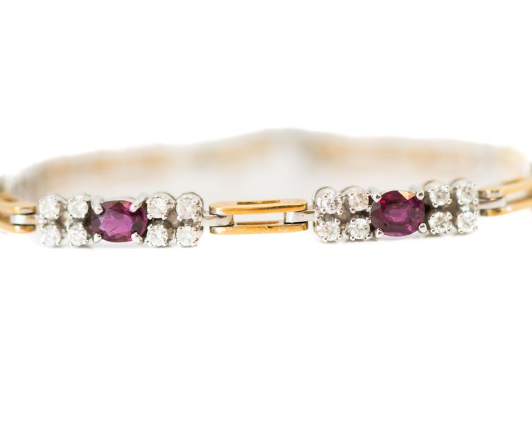 1980s Diamond and Ruby, 18 Karat White and Yellow Gold Two Tone Link Bracelet  Features 32 Round Brilliant Diamonds and 4 Oval Red Rubies. These gorgeous gemstones are set in White Gold and alternate with Yellow Gold links. Each of the 18 Karat