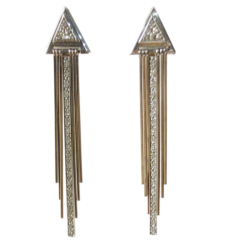 Pair of 14K white gold and diamond fringed 1970's / 1980's Deco revival earrings.  Earrings have a total of seven kinetic fringe, including a strand of diamonds seen center.  Pierced earrings measure 2 3/8