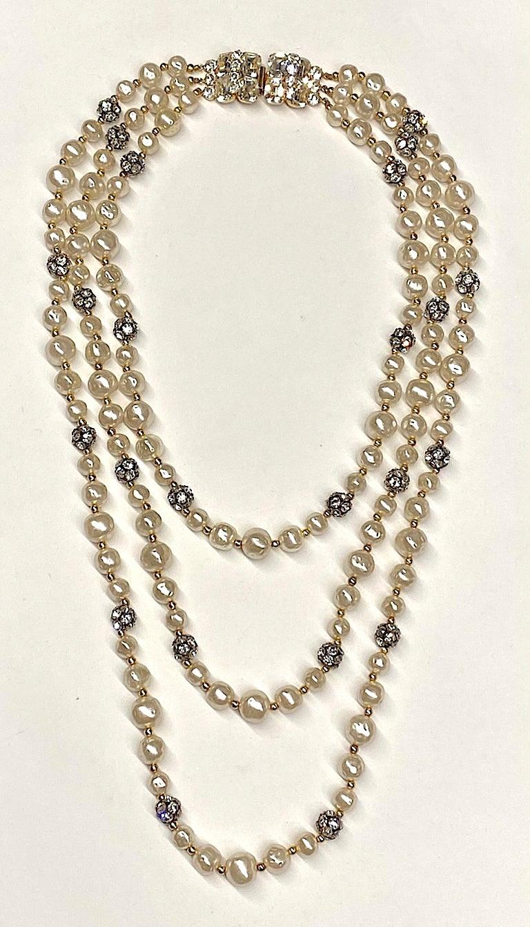 A stunning triple stand faux  pearl and rhinestone bead necklace from the 1980s. The faux pearls are a creamy off white in color and Baroque pearl style in three sizes of 10, 12, and 14 mm. Additionally, every five pearls there is a 12 mm rhinestone