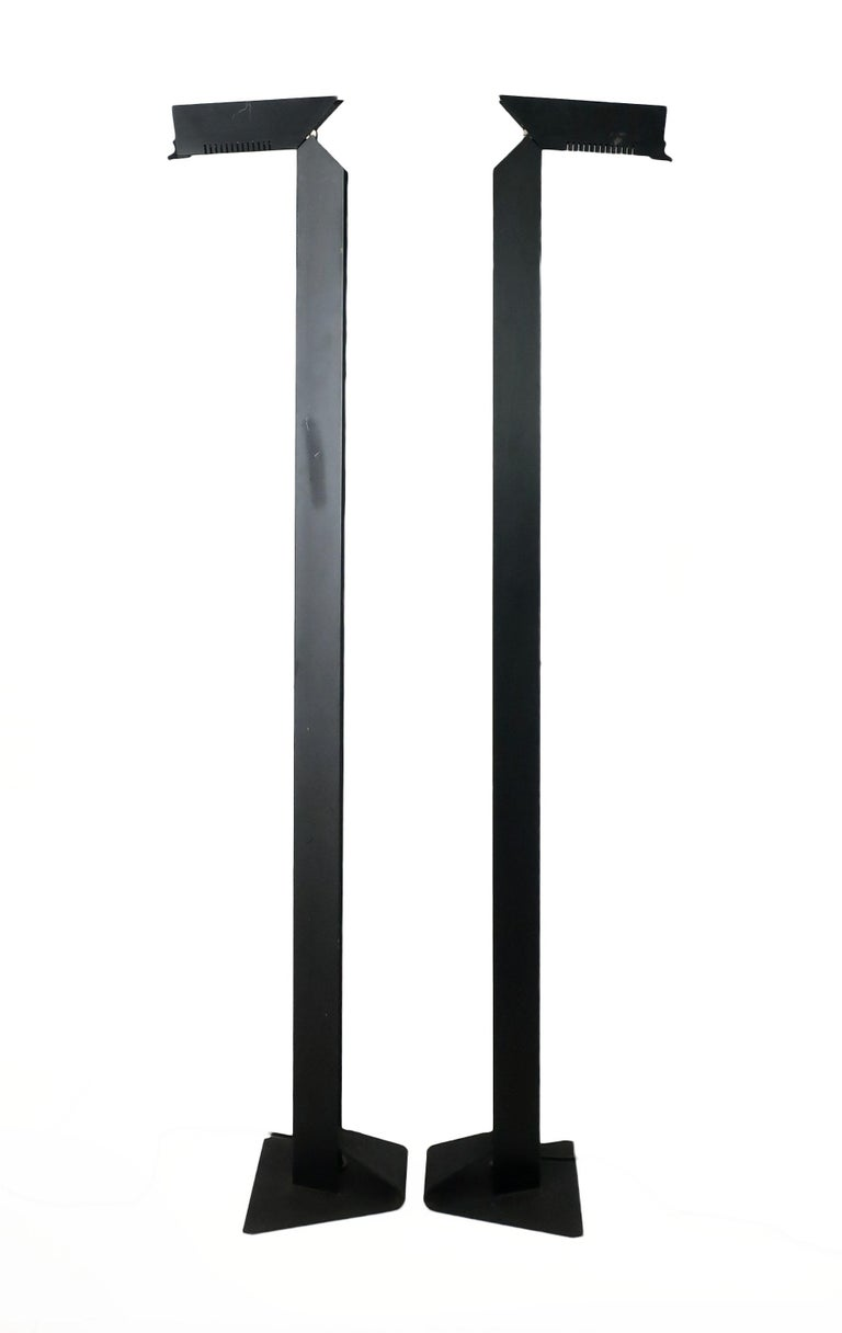 A stunning pair of tall, dark, and handsome Italian postmodern aluminum floor lamps by Skipper Pollux. Set on a cast iron base to ensure stability, this pair of black floor lamps have an extraordinary angular design that allows the halogen light to