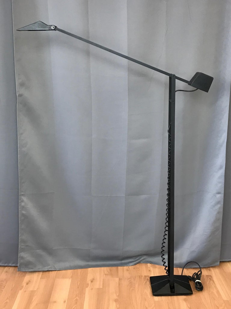 An uncommon 1980s black metal articulated halogen floor lamp by Artup.  Minimalist design, with position able shade and arm, counterweight transformer with toggle switch, and fixed pole in textured black enameled steel. Heavy base is black cast