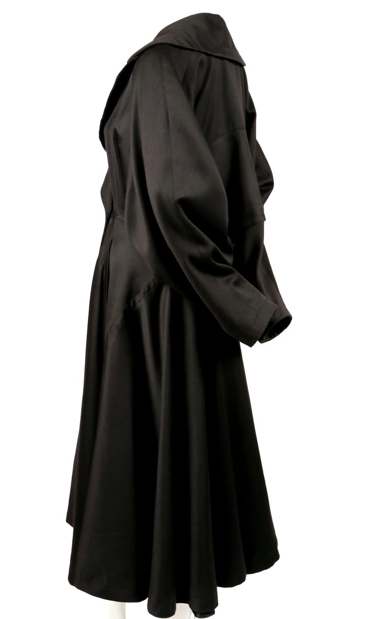 Jet-black, gabardine wool coat with full skirt and uniquely constructed back designed by Azzedine Alaia dating to the late 1980's. Very flattering fit. Coat is labeled a French size 38. Approximate measurements: waist 28-29