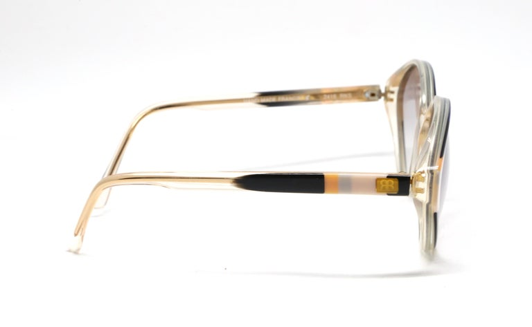 Vertically striped plastic sunglasses from Balenciaga dating to the 1980's. Colors are: royal blue, black, peach, sky blue, cream and red. Approximate measurements: just under 5.75