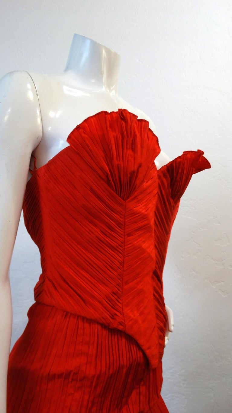 Make A Statement With This Amazing Piece! Circa 1980s, this Bernard Perris couture silk crepe bustier is a beautiful red color and features intricate asymmetrical pleating throughout. The cups on the bustier are high standing and mimic a shell like
