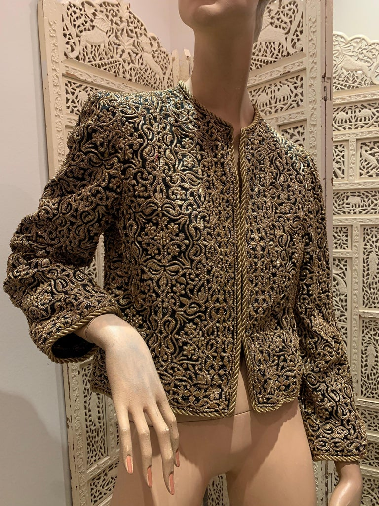A stunning 1980s Bill Blass evening jacket of traditional Indian inspiration. Heavily encrusted all over with chain embroidery gold work. Imported fabric. Gold roping at hems and cuffs. Fully lined with hook and eye closures.
