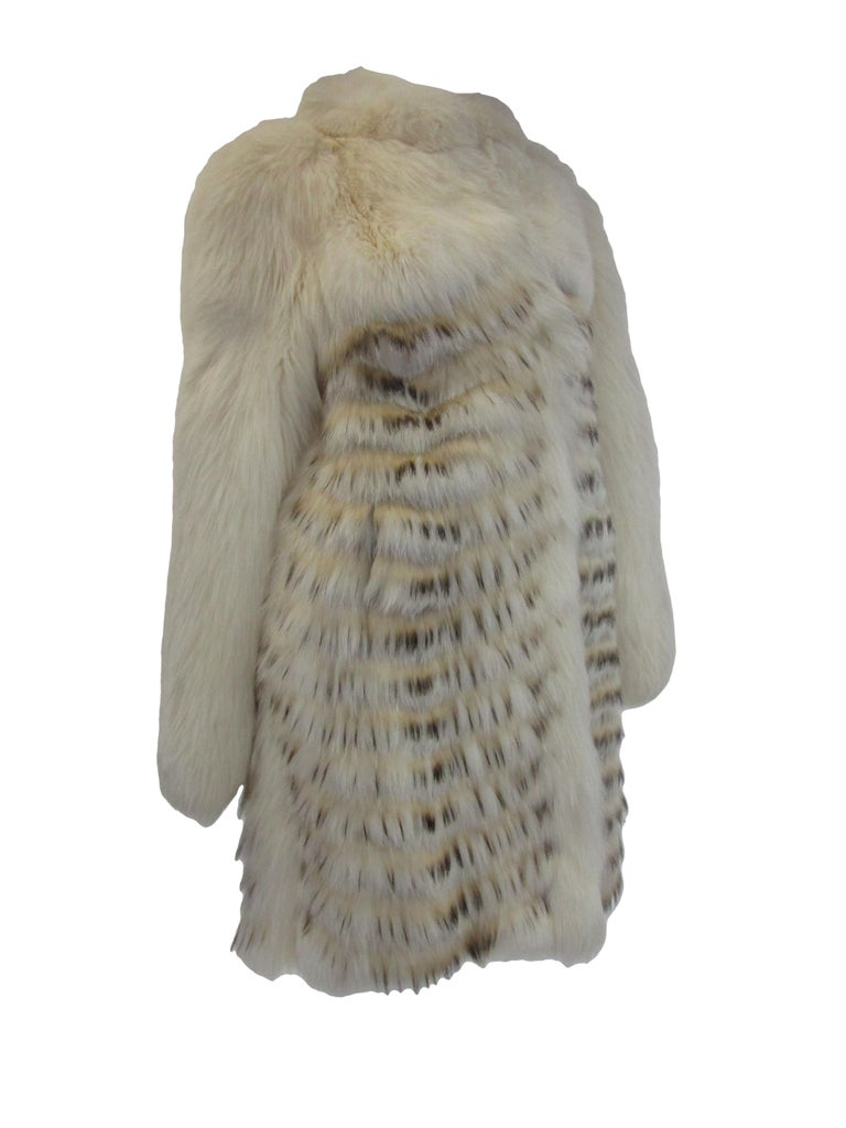 make a statement this winter with a ravishing fur coat from Bill Blass Paris! Perfect for an evening event or just casually strutting your best look off the slopes! The fur billows around the neck with hues of brown, cream and grey cascading down