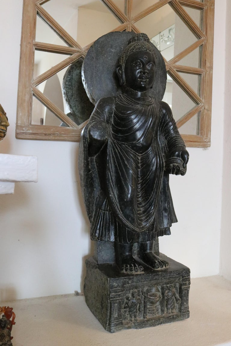 1980s black marble hand carved Buddha sculpture with characteristic robes and aureole, standing on a square base with relief decorations.