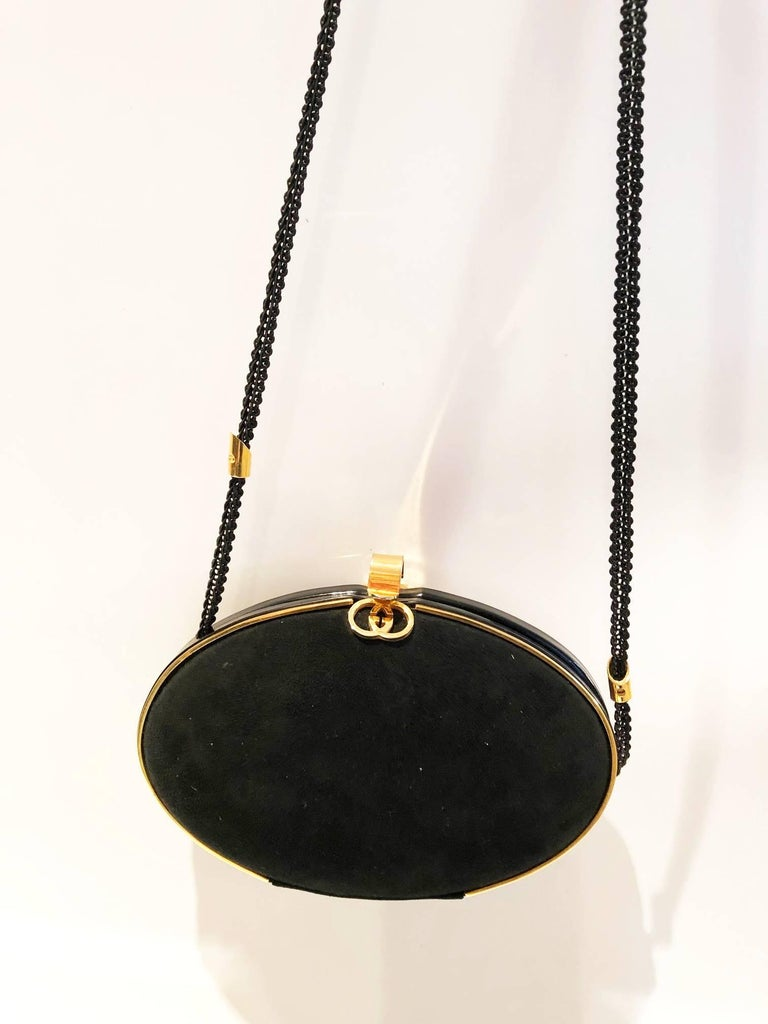Gucci Black Vintage Gold Clutch Bag, black velvet hard shell oval rounded clutch bag, Gold edge trim and GG logo and clip clasp at top. Inside, classic GG printed fabric with small card pocket and poppered string shoulder strap with logo details;