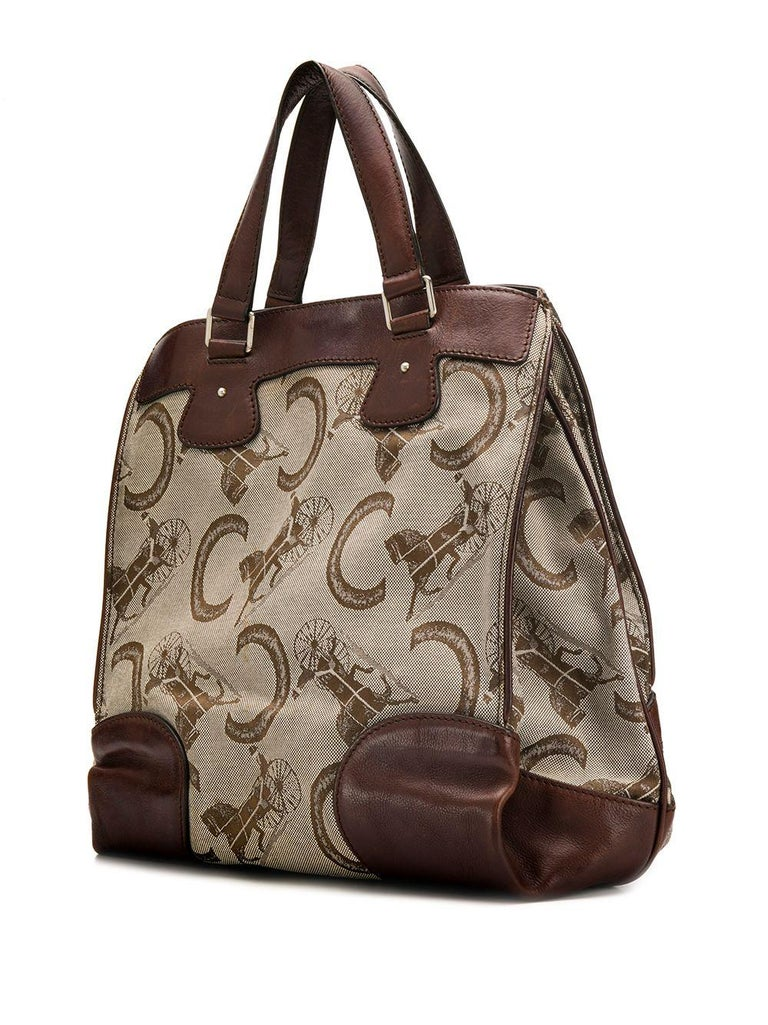1980s Celine brown and beige canvas and leather tote bag featuring a logo horse carriage pattern, accordion pleat design, top handles, a magnetic closure, an internal zipped pocket, a front logo plaque, silver-tone hardware, a horse carriage pattern