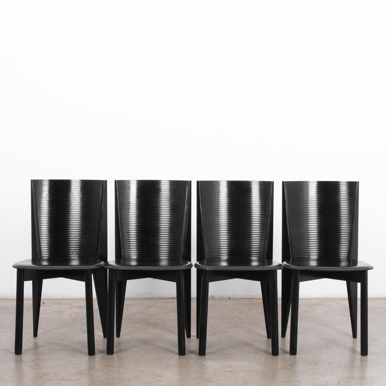 This set of four black wooden chairs by Calligaris was made in Italy, circa 1980. These dining chairs feature a curved back with ridges and leather seats. The tapered and angular rear posts counterbalance the cylindrical front legs of this stylish