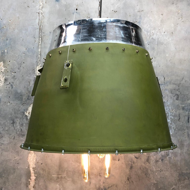 A reclaimed green jet engine cowling from a bombardier Learjet business aircraft which has been recycled and converted into a large ceiling pendant light.  This was originally found on the exhaust of the jet engine. We have both cowlings from the