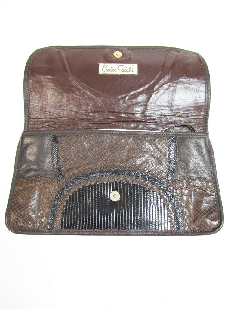 Carols Falchi created this clutch with multiple skins including Lizard, Snake and leather in brown and black. There is a leather strap if you want to use it as a shoulder bag. Large enough for a phone. Can be used for daytime or evening.    Strap