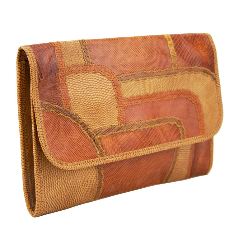 1980s Carlos Falchi tan and brown patchwork rectangular clutch. Envelope style with flap front with gold snap closure. Brown leather interior with single interior slip pocket with zipper. Excellent vintage condition. 12