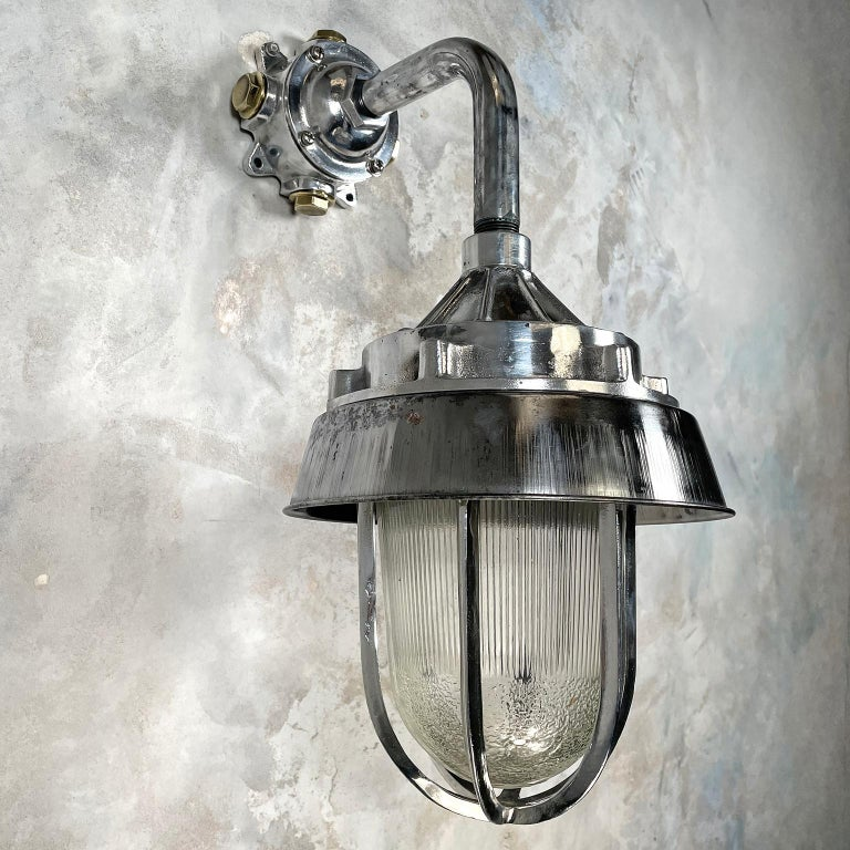Aluminum 1980's Cast Aluminium Cantilever Wall Lamp Reeded Glass, Steel Shade & Cage For Sale