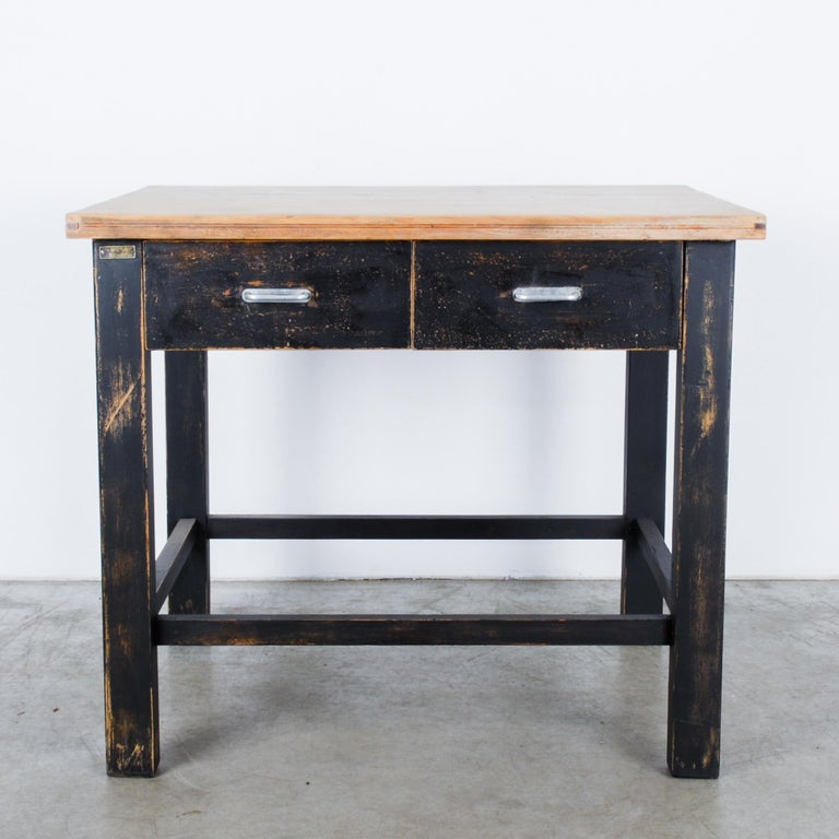 A black patinated wood occasional table from Central Europe, circa 1980. Great for a studio or working space, its double drawers with metal pulls makes it a perfect side table. Bold, heavy furniture started to make a comeback in the 1980s, here