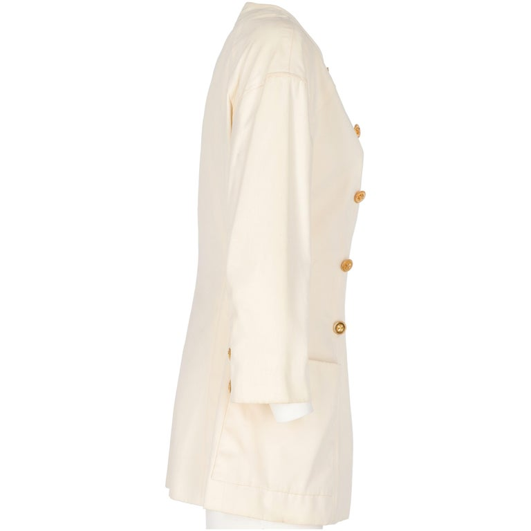 Marvellous Chanel double-breasted jacket in white ivory cotton with a slightly flared cut. It features a crew neck with two metal tiny press-studs under the collar and two decorative buttons in shiny gold-tone metal with thick details. Midi lenght