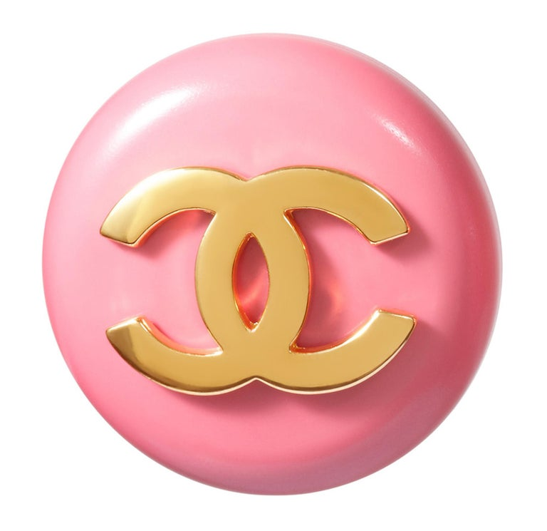 These fantastic 1980s Chanel pink lucite earrings feature a bold gold tone CC motif. Each piece measures 1.4 in diameter and is made of rose pink lucite mounted on a gold-plated backing. The designers signature is located below the clip fastenings