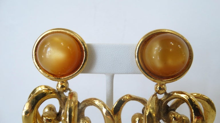 The Most Amazing Lacroix Earrings Are Here! Circa 1980s, these gold plated drop earrings feature two tiered Baroque style scroll hearts and a small amber colored bead hanging from the end. Clip on closures include an amber colored acrylic gem as the