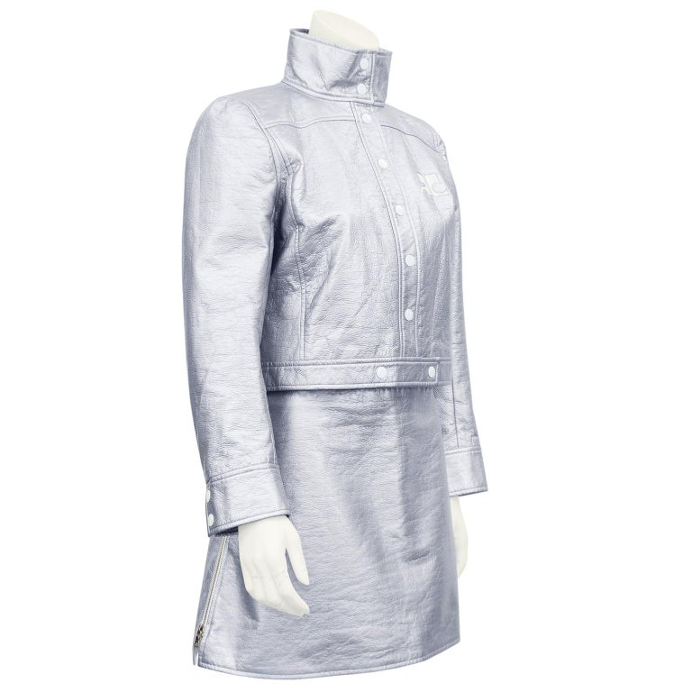 The ultimate Courreges 80's revival look. Iconic silver vinyl Courreges biker jacket and matching mini skirt. Jacket is cropped with standing collar, white snap closures, and white Courreges logo on left side of bust. White lining with small all