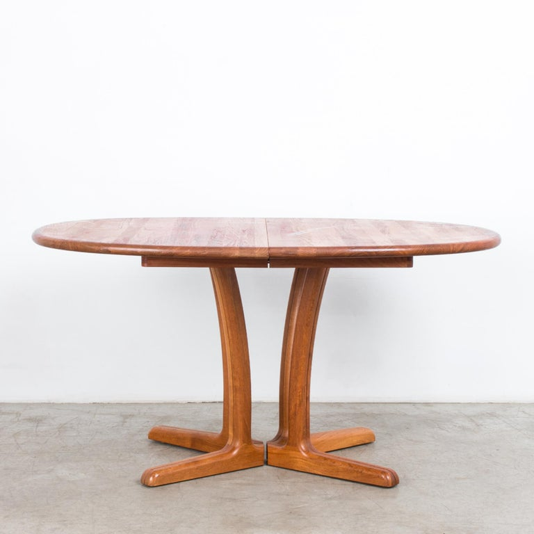 A teak dining table from Denmark, circa 1980. A round tabletop sits atop four legs with distinctive splayed feet. An extra leaf allows the tabletop to be extended to create a long, oval dining table. The wood is a bright caramel color, with the