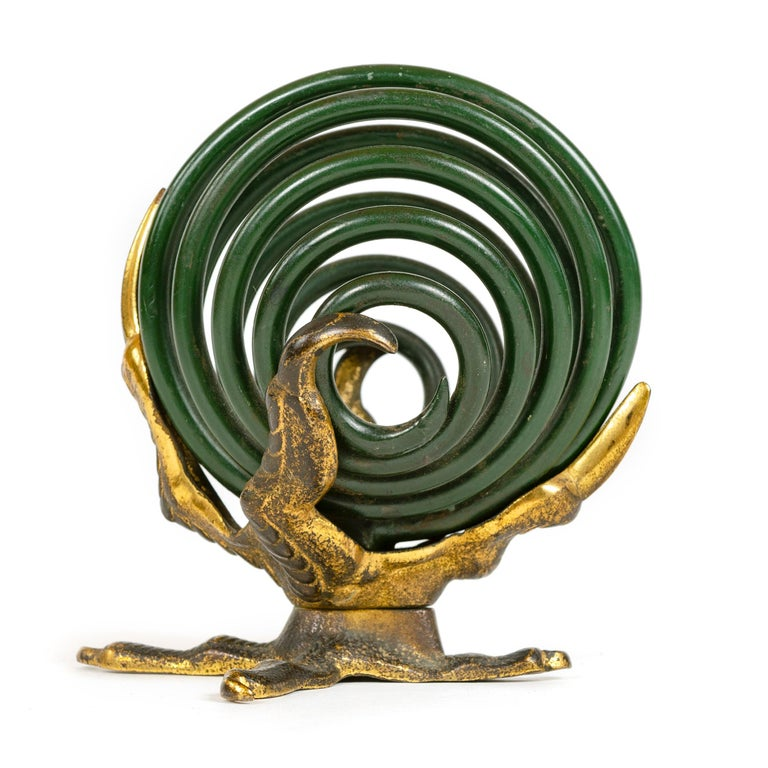 A curious desk accessory useful as a note or letter holder having three bronze talons grasping a coiled, spiral orb made from one continuous strand of thick steel finished in deep green enamel.