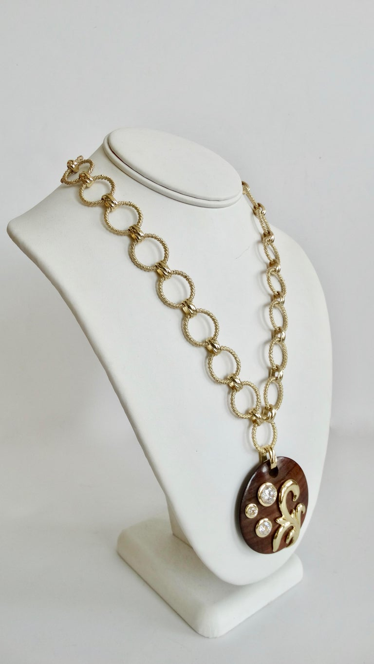 We all need a great vintage jewelry piece in our collection! Circa late 1980s, this Dominique Aurientis necklace features a textured gold plated link chain and a round dark wood stained pendant embellished with three Swarovski crystals and a gold