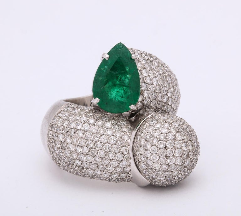 One Ladies 18kt White Gold Large Crossover Bypass Cocktail ring Designed With One Approx. 3 Carat Pear Shaped Emerald. ring Is Also Embellished With Approximately 4 Carts Of Full Cut Diamonds. Large Cocktail Ring Designed In The 1980's In Italy .