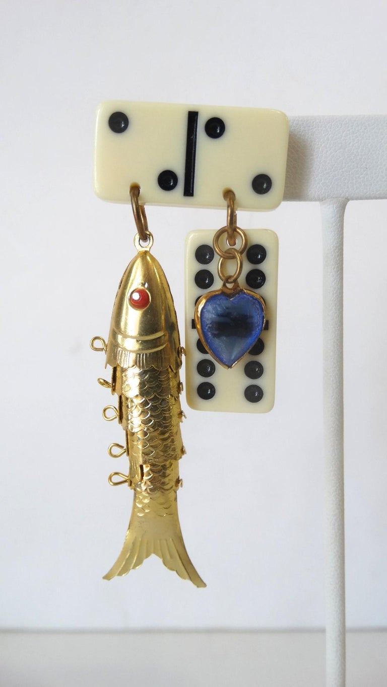 The Most Amazing Earrings Are Here! Circa 1980s, these dangle earrings feature mini dominos, a blue heart charm and a gold plated moveable Chinese fish pendent. The fish pendent includes red eyes and great textural detail. Features pierced backs.