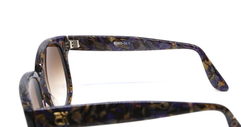 Vivid purple and bronze mosaic sunglasses with gold-toned EK logos at temples and golden brown hued lenses from Emmanuelle Khanh dating to the late 1970's, early 1980's. Oversized frames work well for a medium or larger sized face. Approximate