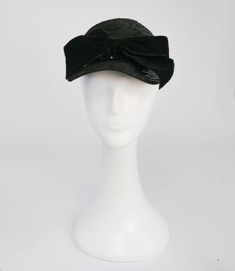 1980s Eric Javits Black Sequin Cap w/ Velvet Bow. Black cap encrusted in scequin and garnished with a velvet bow. 21 to 22 inch circumference