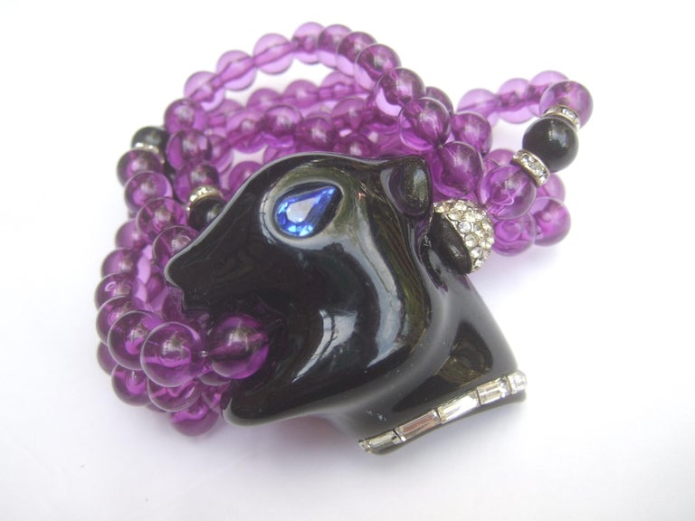 1980s Exotic figural panther's head jeweled crystal resin beaded bracelet. Small Size  The unique bracelet is designed with a smooth black lucite panther's head with a sapphire blue color crystal eye. Accented with a clear baguette crystal  collar.